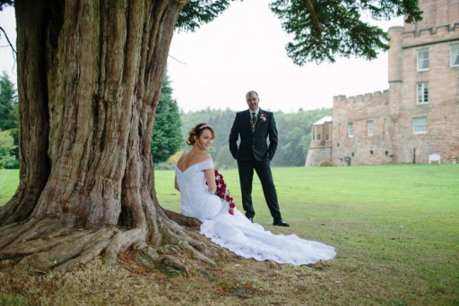 Photo of bride and groom beneath ancient tree in the grounds of a Scottish castle
