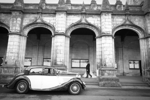 Photo of a vintage wedding car with bride and groom in background