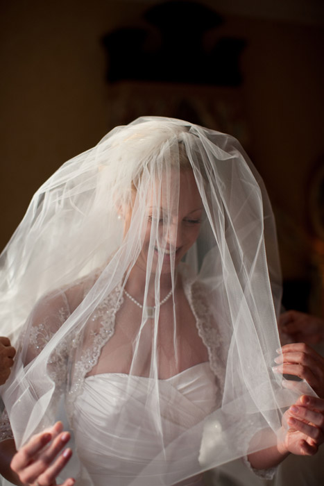 Photo of a bride smiling beneath her veil