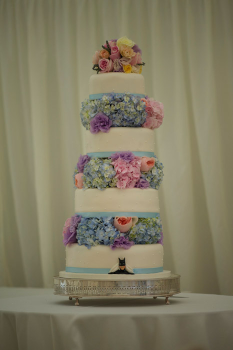 Photo of four tiered white wedding cake with flowers between each tier
