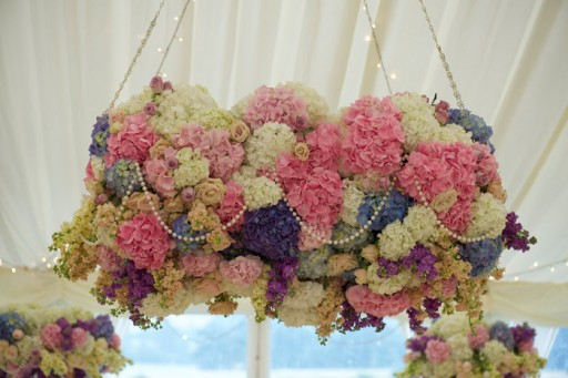 Photo of a cloud of cream, pink and lilac flowers with pearls suspended from the ceiling at a wedding reception