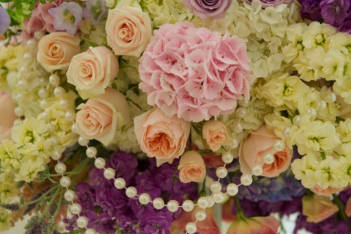 Photo of wedding flowers in shades of pink, purple and cream with strings of pearls