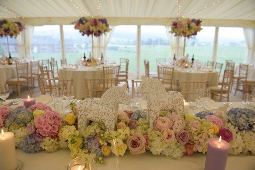 Photo of marquee interior styled for a wedding reception with flowers and candles in pastel shades
