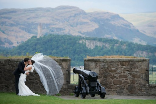 Bride and groom embracing in front of the parapet of a Scottish castle