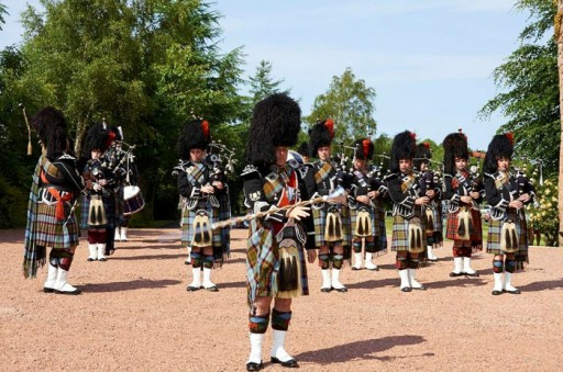 Photo of a pipe band in full Highland regalia playing a beating retreat