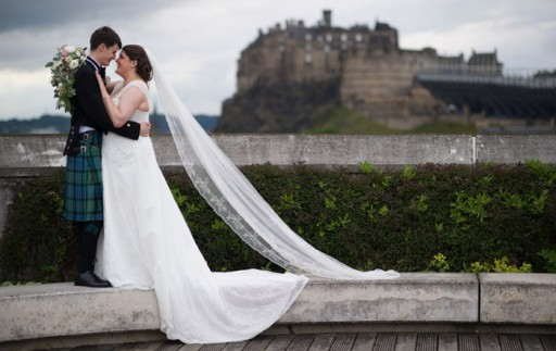 Bride and groom embracing on rooftop with Edinburgh Castle in the background