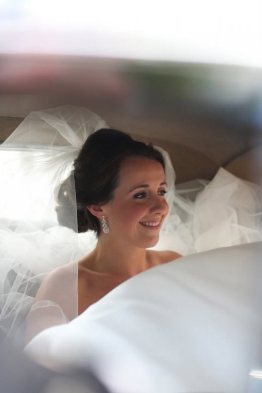 Photo of bride sitting in wedding car