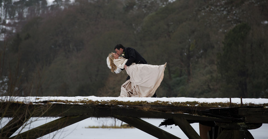 Photo of bride and groom embracing on a snow covered wooden bridge