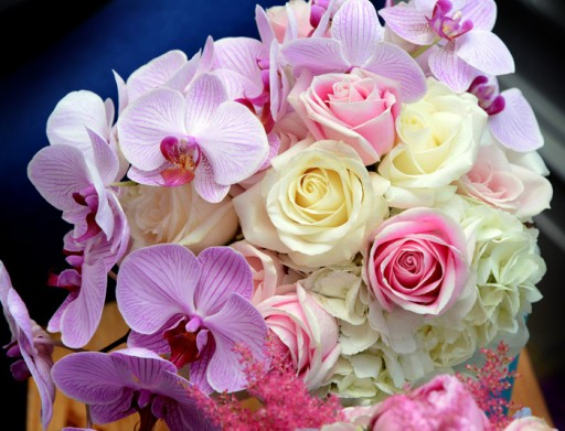 Close up photo of a wedding bouquet with ivory and pink roses and lilac orchids
