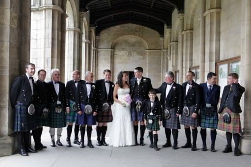 Photo of bride and groom with kilted wedding guests