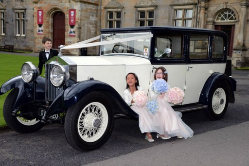 Photo of flower girls sitting giggling on the running board of a vintage wedding car