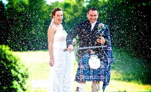 Photo of bride and groom outside spraying champagne