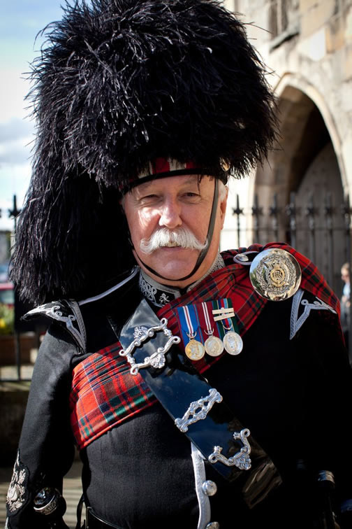Photo of a pipe band member dressed in full Highland regalia