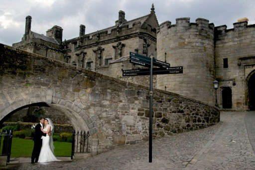Photo of bride and groom embracing beneath arch in Scottish castle grounds