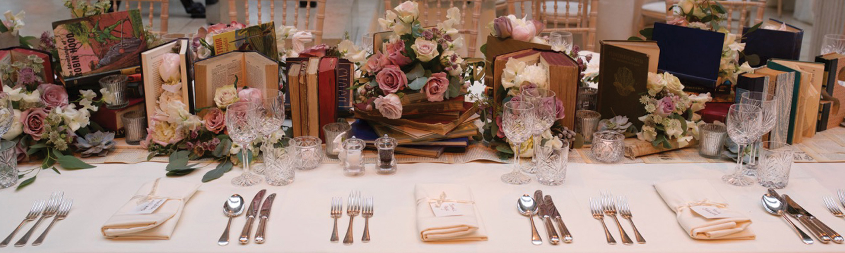 Photo of the head table at a wedding reception decorated with flowers and books