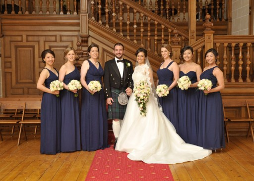 Photo of bride, groom and bridesmaids standing in front of a panelled wooden staircase
