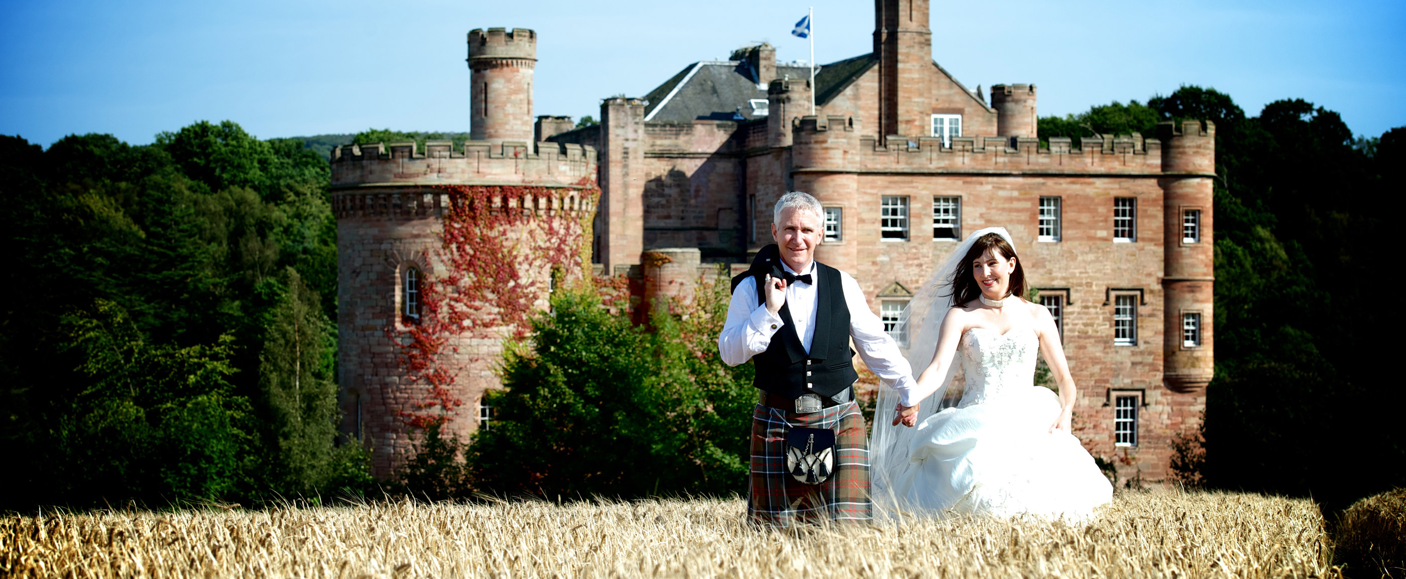 Photo of a bride and groom hand in hand on their wedding day, walking through a barley field with a Scottish castle in the background