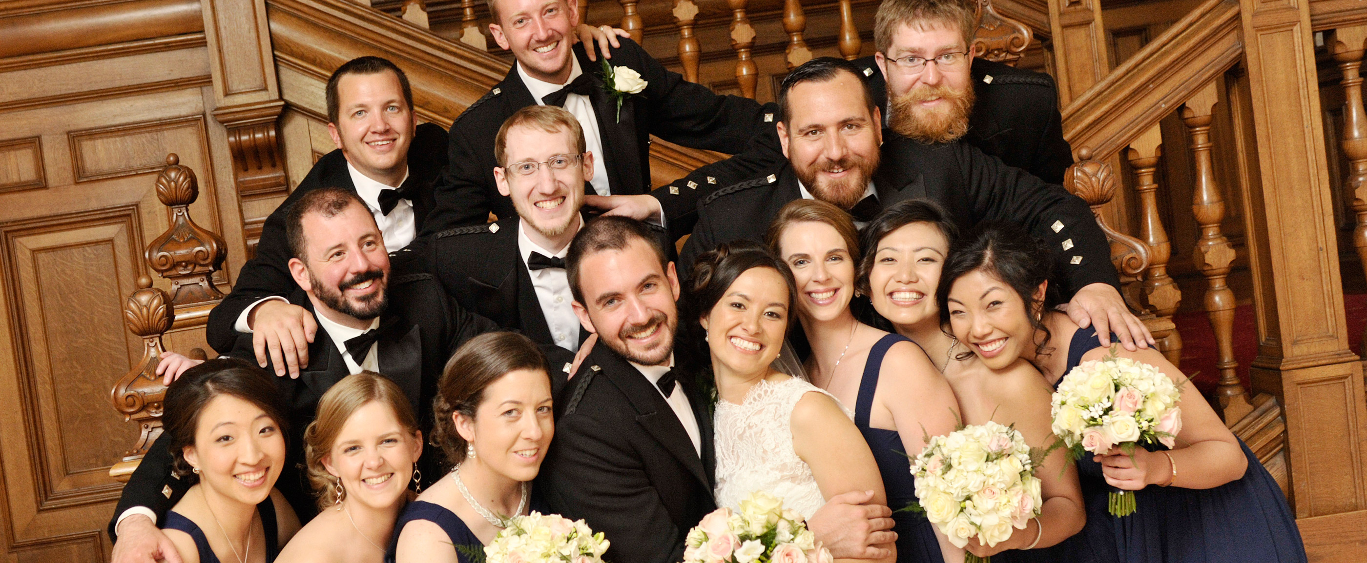 Photo of bride and groom with bridesmaids in dark blue dresses and guests in highland dress in front of wood paneled stairs