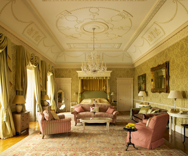 Photo of sumptuous bedroom in Archerfield House. The colours are pale pink, green and gold with heavy drapes and large chandelier