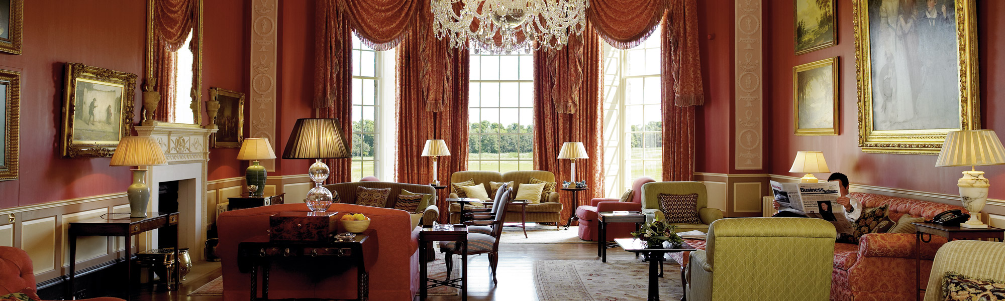 Photo of large lounge at Archerfield House, with open fire, sofas, lamps and chandelier