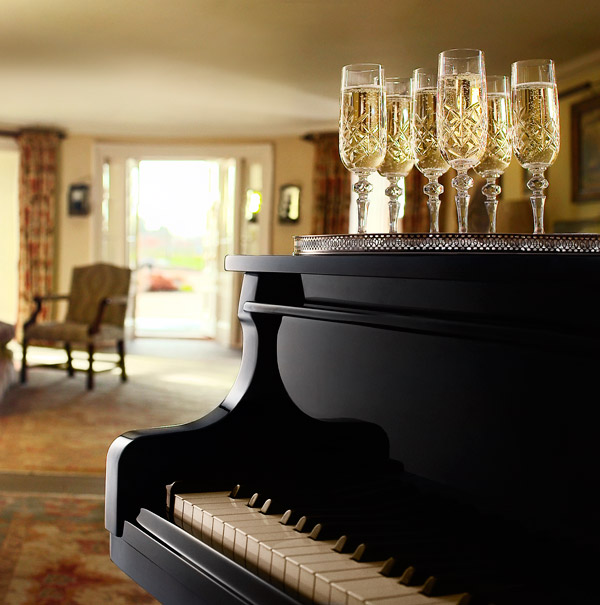 Photo of a black grand piano with a silver tray of crystal champagne flutes sitting on top