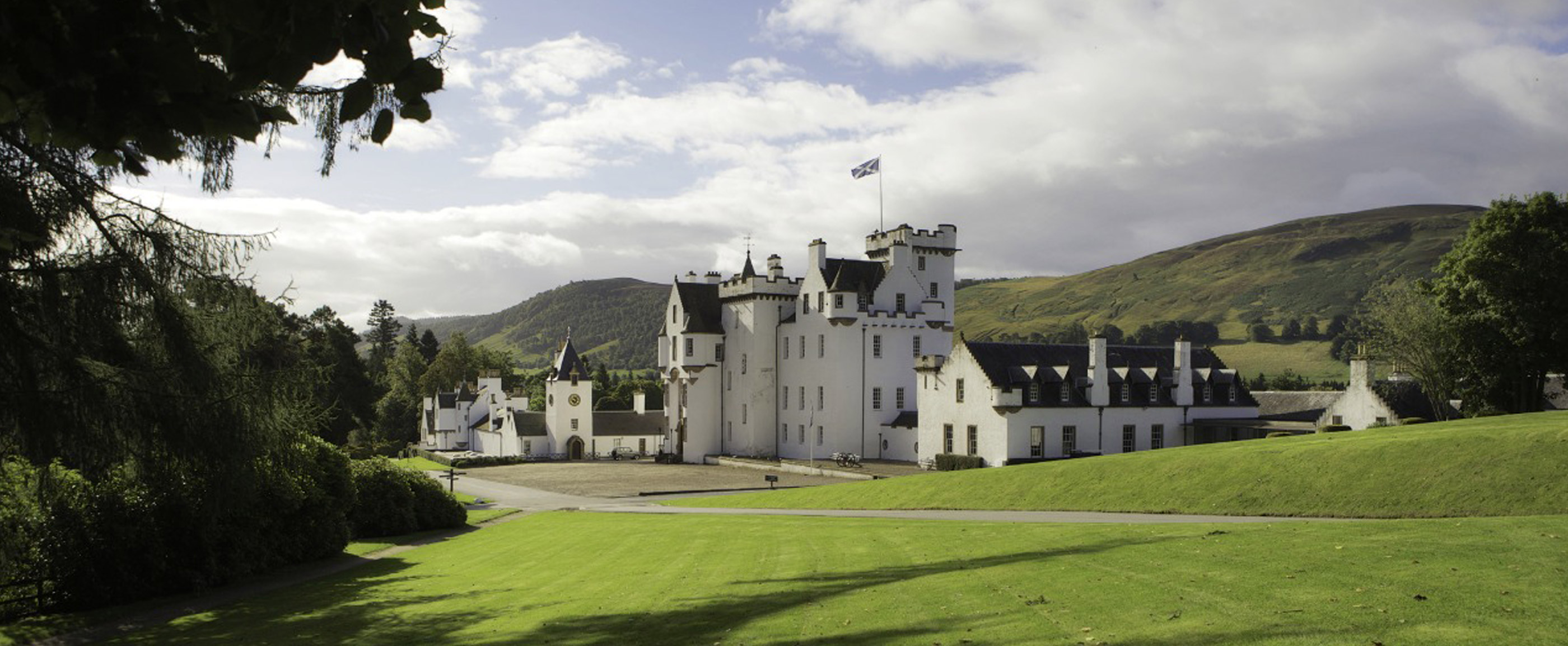 Photo of Blair Castle, a white washed, turreted castle in the Scottish Highlands