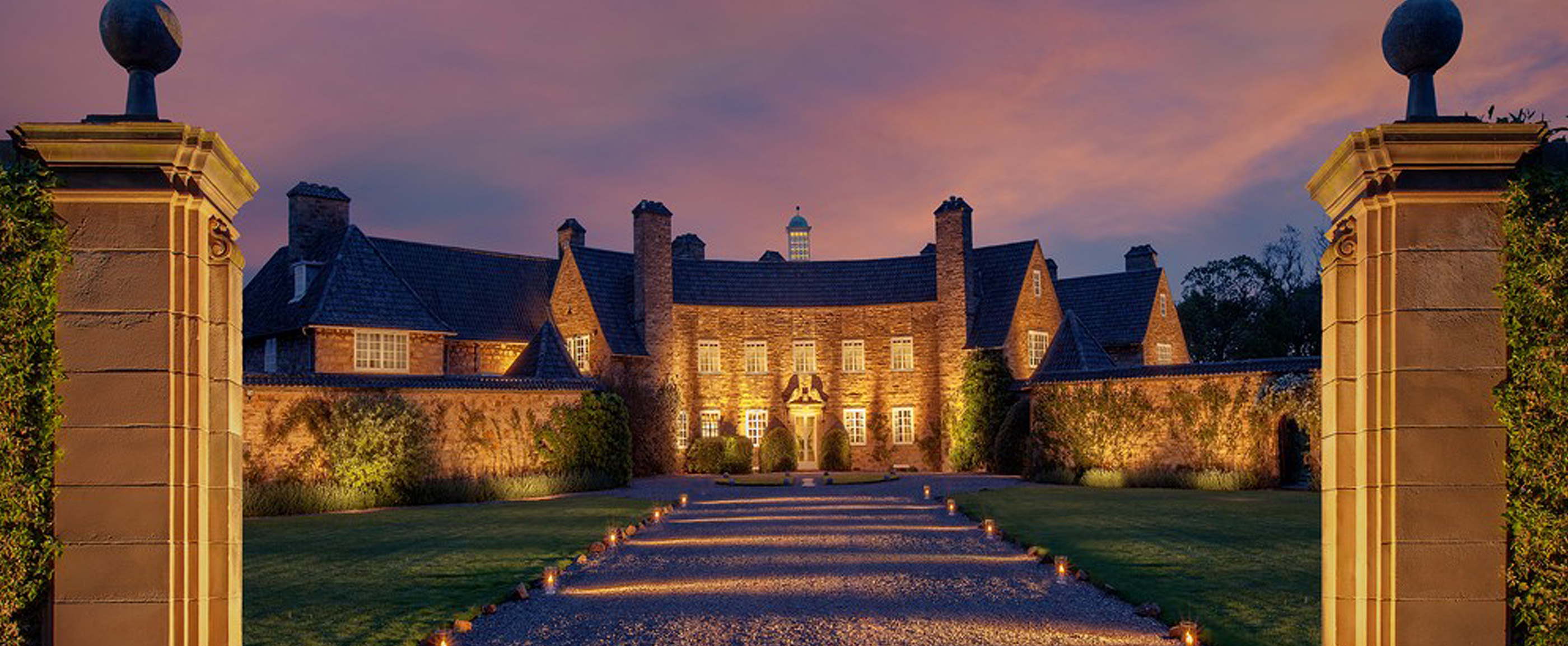 Photo of the exterior of Greywalls House, illuminated in the evening.