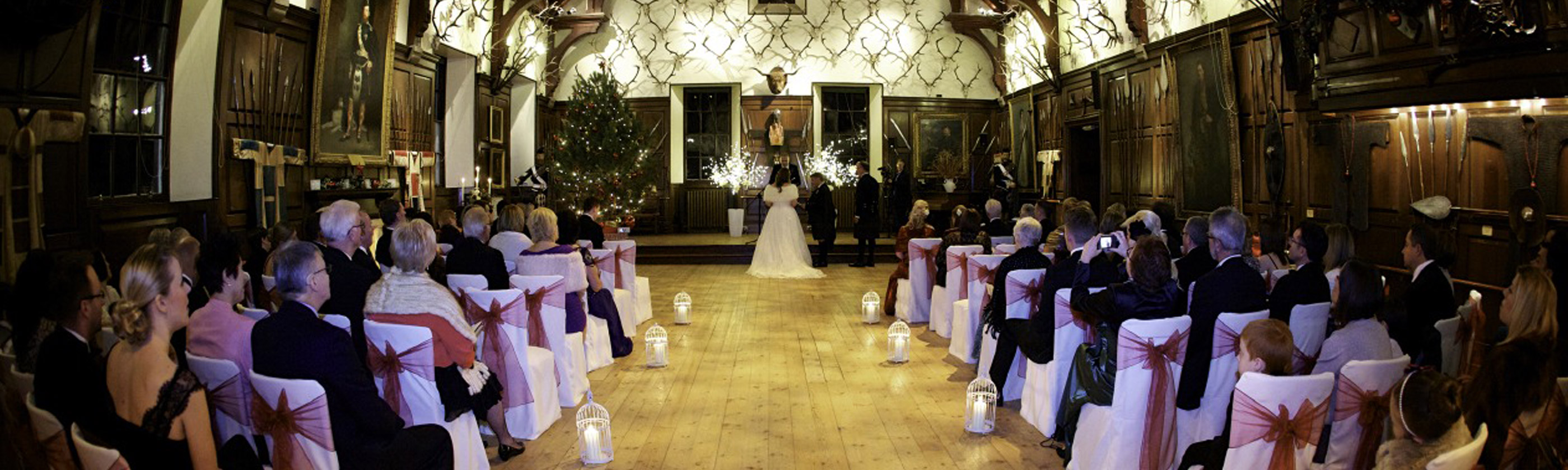 Photo of a wedding ceremony taking place in one of the grand wood paneled halls in Blair Castle