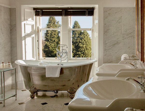 Photo of a luxurious en-suite bathroom in Cromlix House Hotel with marble floor, twin sinks and free standing bath