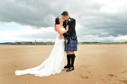 Photo of bride and groom kissing on the West Sands in St Andrews