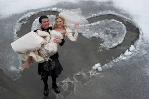 Photo of groom carrying bride in the snow
