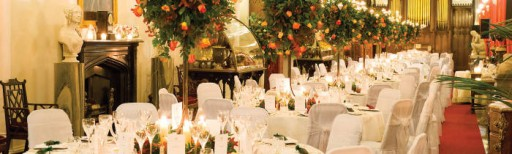 Photo of tables at a wedding reception with white linens and elevated table flower arrangements in orange tones with greenery and tealights