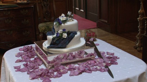 Two tier Scottish wedding cake with tartan decoration, flower petals and sword